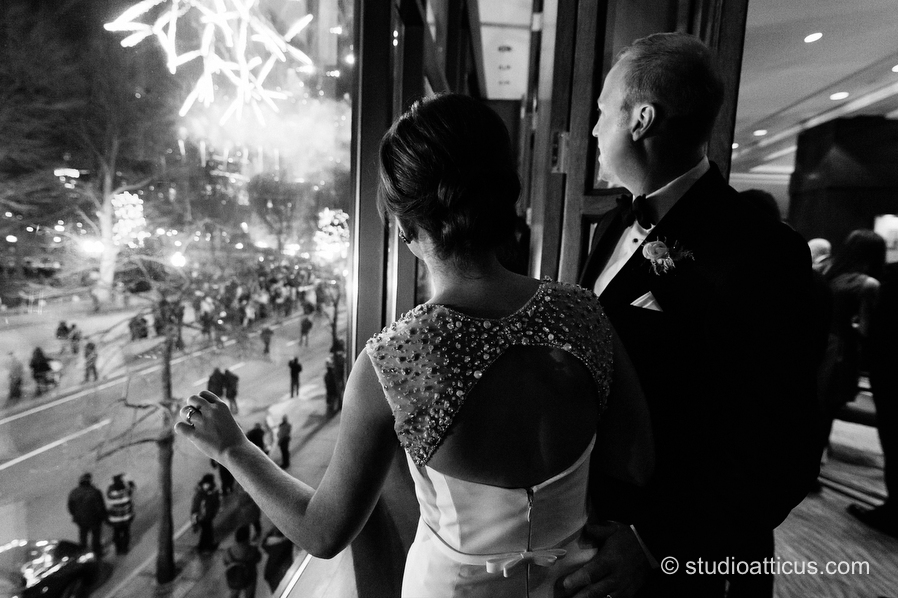 The bride and groom watch First Night fireworks during cocktail hour at their wedding at the Four Seasons Hotel in Boston.