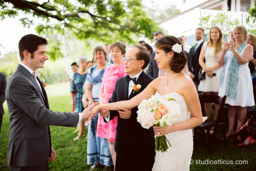 The father gives away the bride at an outdoor wedding ceremony at Puakea Ranch in  Hawaii