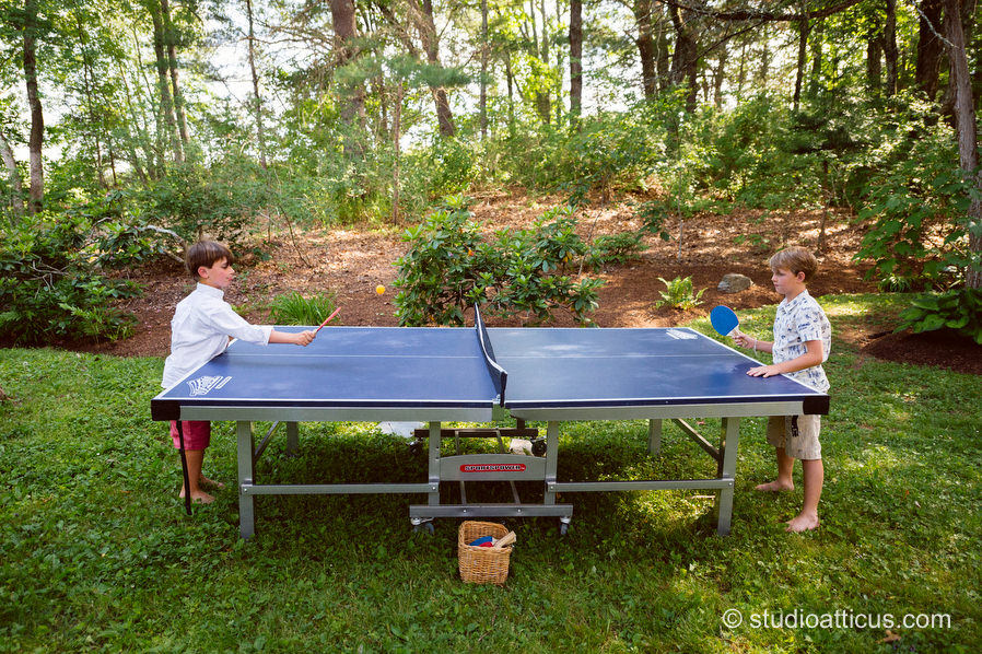 guests play ping pong at a backyard wedding in Concord MA.